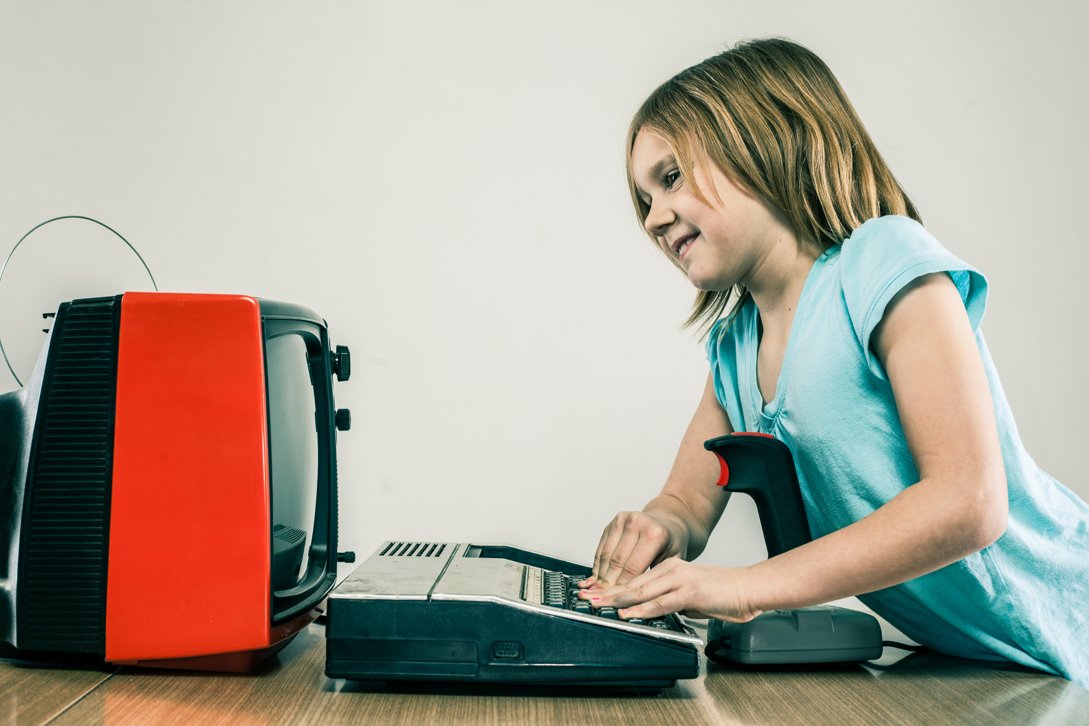 A little girl playing vintage video games from the 1980s on a retro TV and joystick controller