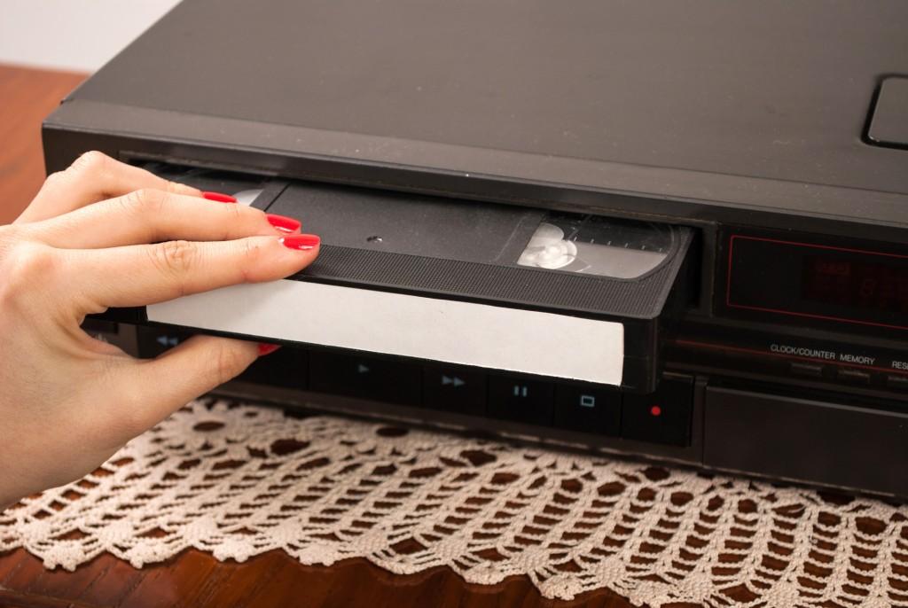 Girl hand inserting blank VHS cassette in old video recorder