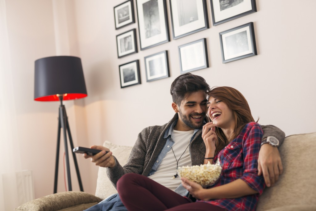 Couple in love sitting on a living room sofa, watching TV and eating popcorn, man switching channels with remote control.