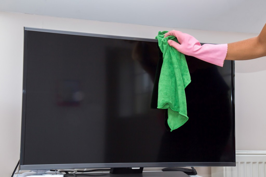 Hand in protective glove carefully cleaning TV screen from dust.