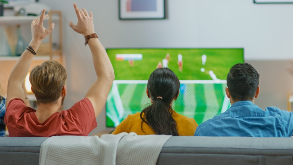 At Home Diverse Group of Sports Fans Sitting on a Couch Watching Important Soccer Game on TV, They Cheer for the Team, Celebrate Victory after Team Scoring Winning Goal. Friends Hugging.