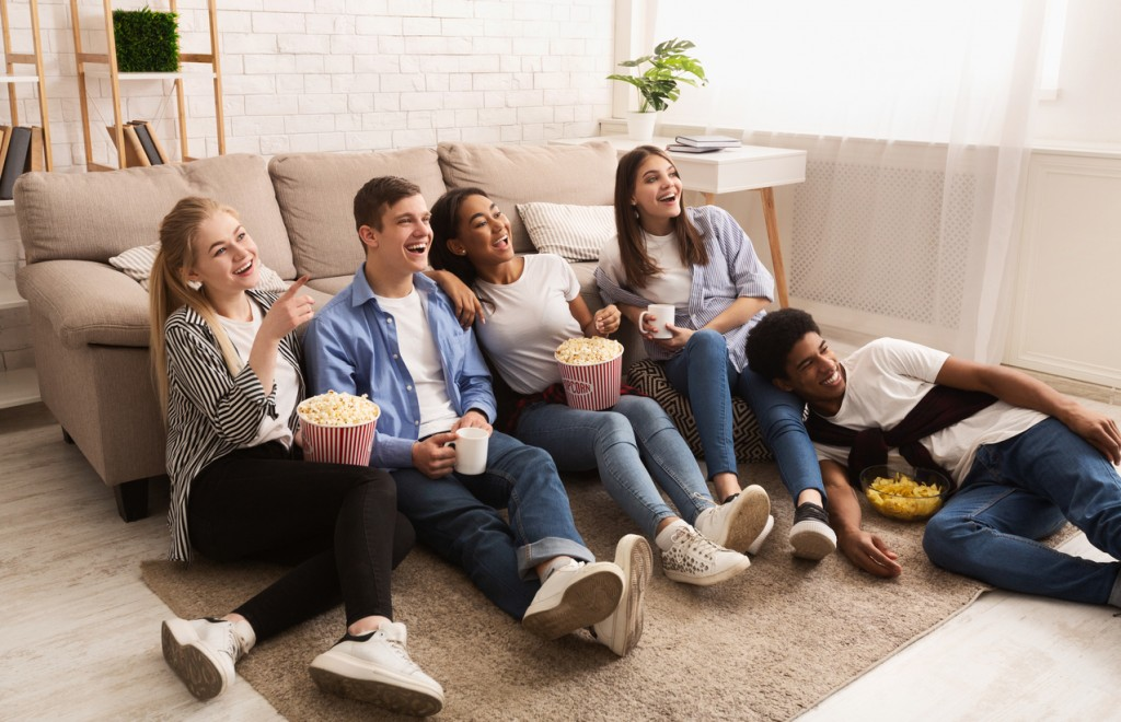 Happy friends watching comedy film and eating popcorn
